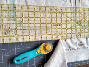 Trimming Fabric Quilt with Ruler and Rotary cutter