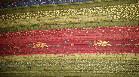 Fabric jelly roll strips sewn together to create one solid fabric panel.