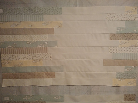 FAbric strips sewn together and placed on a design wall to check placement before sewing last section