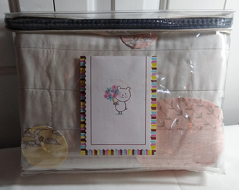 Folded quilt in vinyl zippered bag with card that includes quilt care instructions