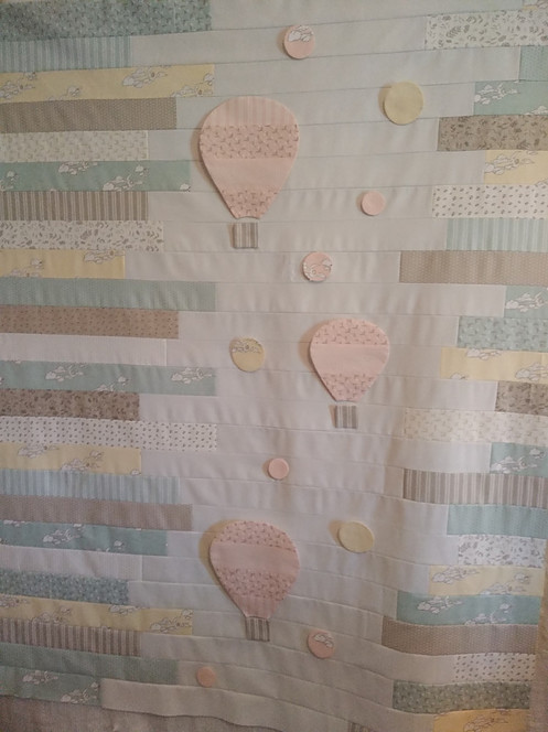 Quilt top made from jelly roll strips and applique hot air ballons and bubbles