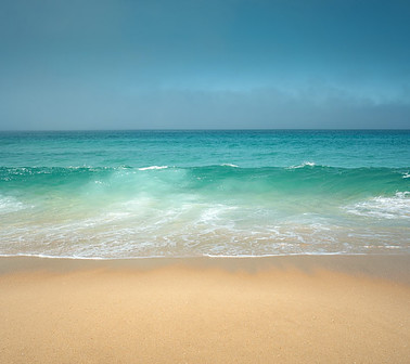 Blue and green waves of ocean water and light brown sandy beach