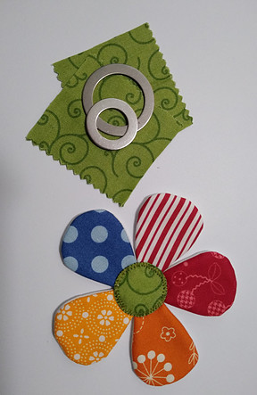 Green fabric squares, applipop round templates, colorful fabric flower with green applipop circle in the middle