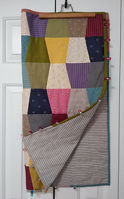 Small quilt made from multi colored scraps of fabric.  Quilt clips used to hold binding in place until stitched in place