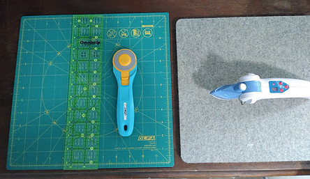 12' square rotating cutting mat, 45 rotary cutter, 2.5' x 12.5' ruler and Dritz mini iron on gray wool pressing mat