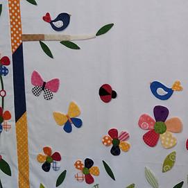 Applique flowers, birds, butterflies on quilt background