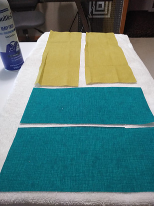 Blue and green fabric rectangles on a white towel eady to be starched