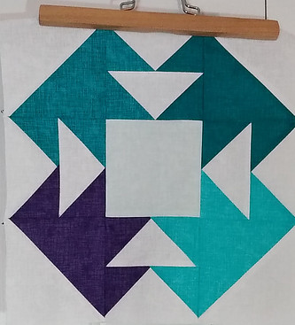 Blue, green and white fabric sewn together to form a quilt block