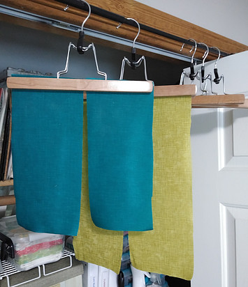 Starched blue and green fabrics hanging to dry