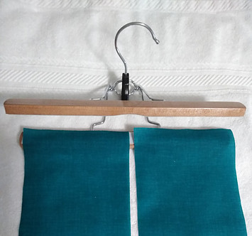 Starched blue fabric positioned to hang on trouser hanger to dry