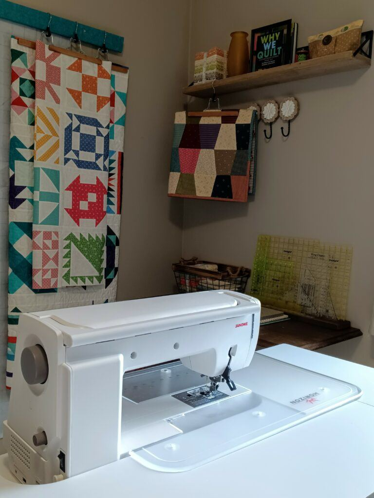 A corner of my sewing room showing my machine, rulers and finished quilts and quilt tops